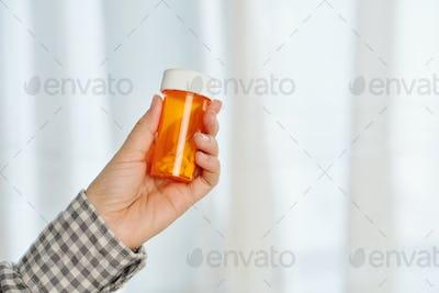 Hand with pills jar