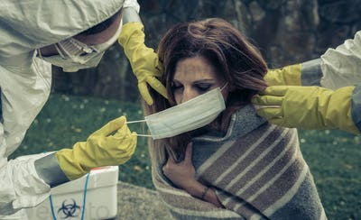 People in bacteriological protective suits putting a mask on woman