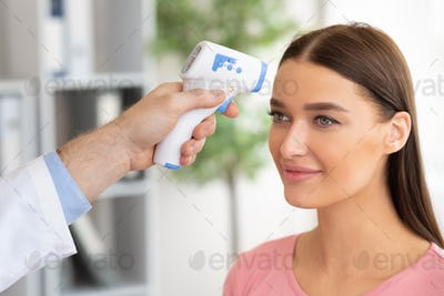 Doctor checking temperature of woman using infrared thermometer