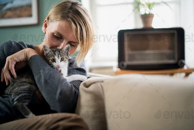 Portrait of woman with cat relaxing indoors at home, mental health care concept.