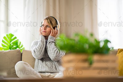 Portrait of woman with headphones relaxing indoors at home, mental health care concept.