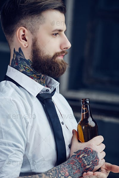 Bearded man with tattooes on his arm.