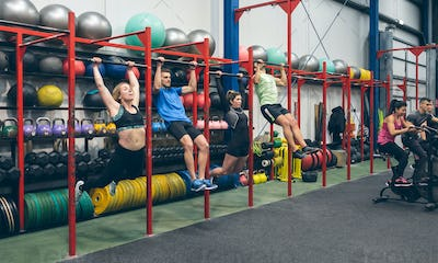 Athletes doing pull ups and air bike in the gym