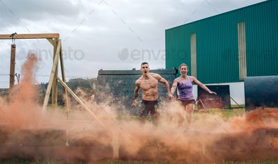 Athletes jumping finish line of an obstacle course