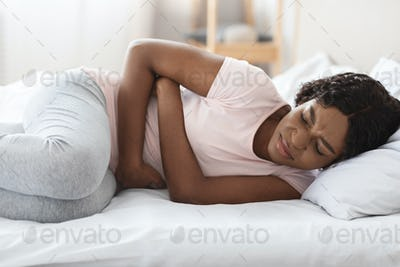 Young black woman touching her tummy, having pain