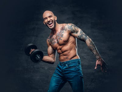 Positive shaved head shirtless male dressed in a jeans holds the