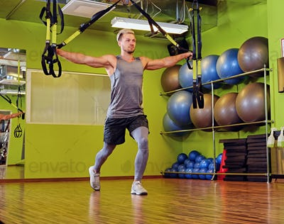 Blond athletic male doing trx straps exercises in a gym club.