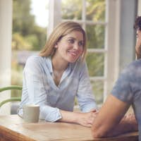 Couple Meeting For Date In Coffee Shop Viewed Through Window