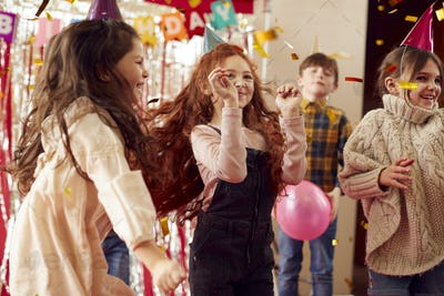 Group Of Children Dancing As They Celebrate At Birthday Party With Paper Hats