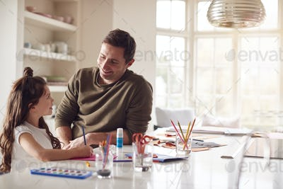 Daughter At Home With Father Having Fun Making Craft Together