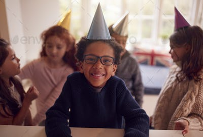 Portrait Of Children Celebrating Birthday With Group Of Friends At Home