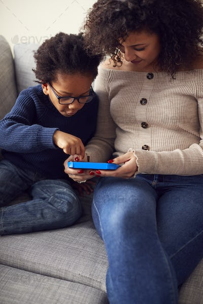 Mother And Son Sitting On Sofa At Home Playing Computer Game Together On Hand Held Device At Home