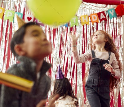 Group Of Children Celebrating At Birthday Party With Paper Hats Playing With Balloons