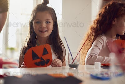 Portrait Of Daughter At Home With Father Having Fun Making Halloween Decoration Together