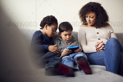 Mother And Sons Sitting On Sofa At Home Playing Computer Game Together On Hand Held Device At Home