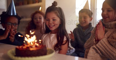 Girl Celebrating Birthday With Group Of Friends At Home Being Given Cake Decorated With Sparkler