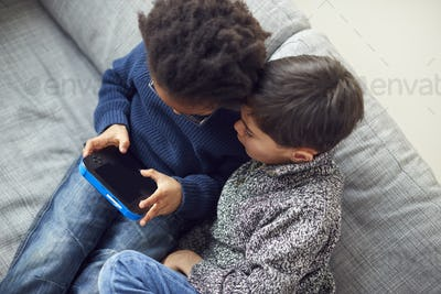 Overhead Shot Of Two Boys Gaming Together On Hand Held Devices At Home