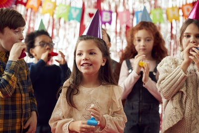 Group Of Children Celebrating At Birthday Party With Paper Hats And Party Blowers