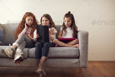 Group Of Girls With Friends Sitting On Sofa At Home Playing On Digital Tablet And Mobile Phones
