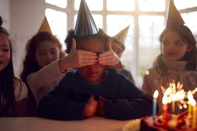 Boy Celebrating Birthday With Group Of Friends At Home Being Given Cake Decorated With Sparkler