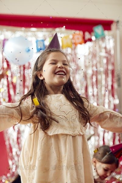 Girl In Party Hat Celebrating At Birthday Party With Glitter And Gold Confetti