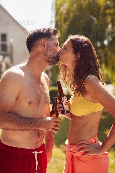Loving Couple Wearing Swimming Costumes Standing In Pool In Summer Garden At Home Drinking Beer