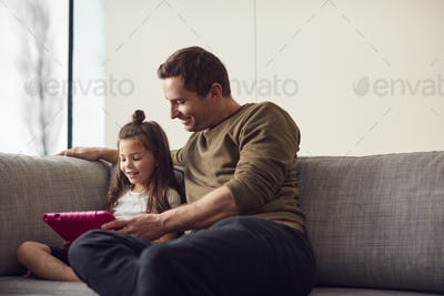 Father And Daughter Sitting On Sofa At Home Playing Together On Digital Tablet In Pink Case At Home