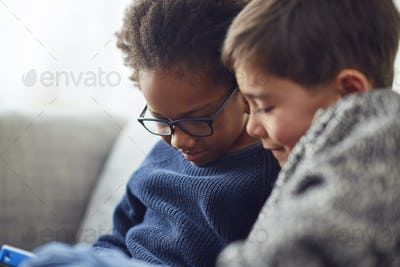 Two Boys Gaming Together On Hand Held Devices At Home