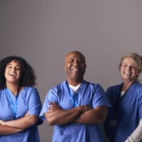 Studio Portrait Of Three Members Of Surgical Team Wearing Scrubs Standing Against Grey Background