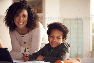 Portrait Of Mother Helping Son With Homework Sitting At Kitchen Counter Using Digital Tablet