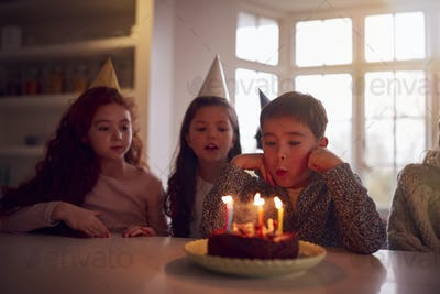 Boy Blowing Out Candles On Cake As He Celebrates Birthday With Group Of Friends At Home