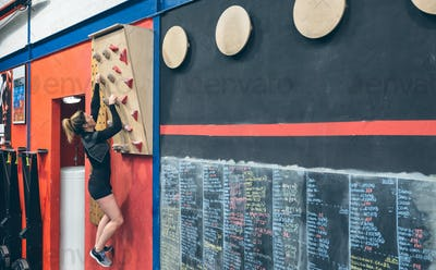 Woman hanging on the climbing wall