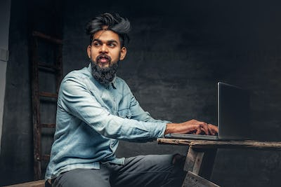 Stylish  Indian male working with laptop.