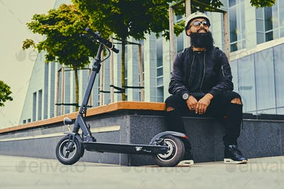 A man relaxing on a bench after riding by electric scooter.