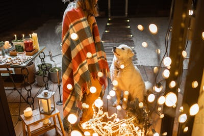 Woman on self-isolation celebrating New Year holidays with her dog at home