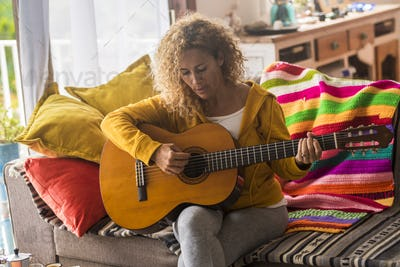 Young adult woman at home learning to play guitar - people and music concept