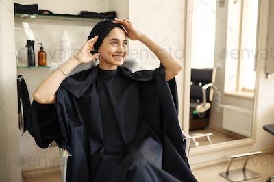 Smiling female customer in hairdressing salon