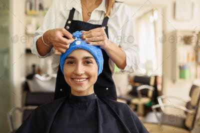 Hairdresser puts towel on woman's hair, front view