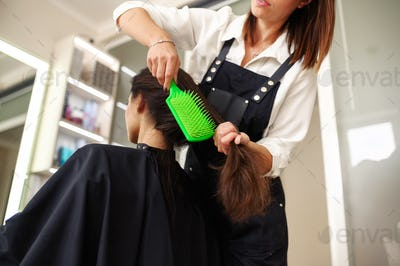 Female customer combs hair in hairdressing salon