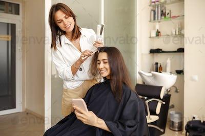 Hairdresser straightens woman's hair, hairsalon