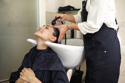 Hairdresser washes woman's hair, hairsalon