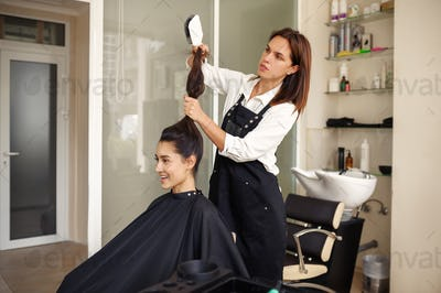 Hairdresser and happy woman, hairdressing salon