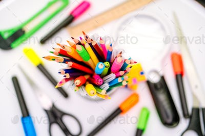 Colored pen and pencils in a clerical case on white background