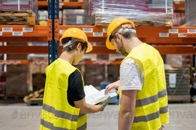 Warehouse workers looking on documents and checking list of packages
