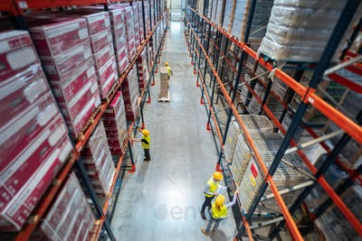 Warehouse workers at work between rows of tall shelves full of packed boxes, top view