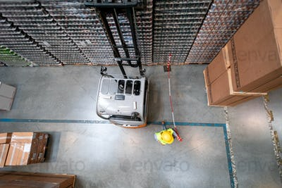 Forklift in warehouse at work, above view