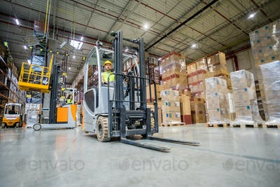 Forklift operator during work in large warehouse