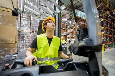 Focused asian warehouse worker with forklift at work