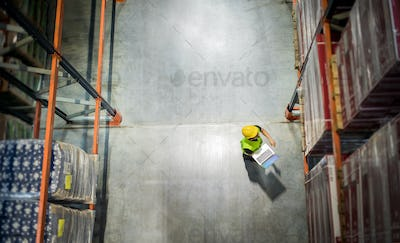 View from above of warehouse worker with laptop at work