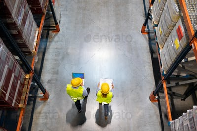 Warehouse workers consult delivery plans using laptop and electronic database